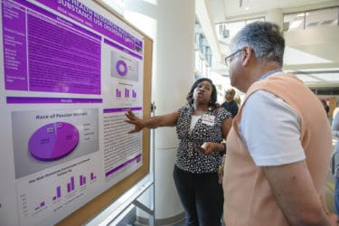 Kisa Vaughn, M.P.A., presents her poster to Reza Hakkak, Ph.D., on the Passion Project, which showed how additional health resources can improve health in African-American women with substance use disorder.