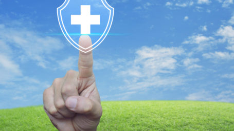 Hand pressing cross shape with shield flat icon over green grass field with blue sky, Business healthy and medical care insurance concept